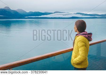 Alaska cruise travel tourist looking at mountains landscape from balcony deck of ship. Inside passage Glacier bay scenic vacation travel woman enjoying scenery from boat.