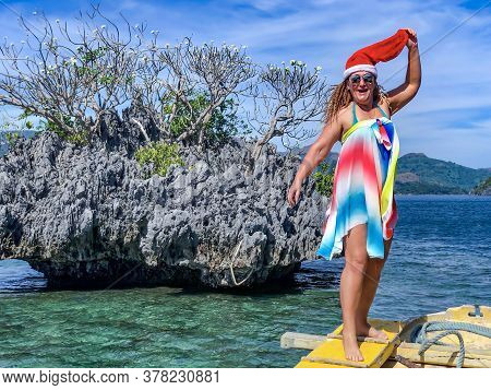 Joyful Smiling Woman In A Multicolored Pareo And With A Santa Claus Hat On Her Head On Tropical Coro