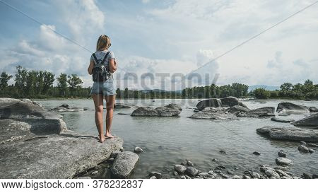 Tourist Traveler With Black Backpack. Hiker View From Back Looking On Hills And Mountain River Lake,