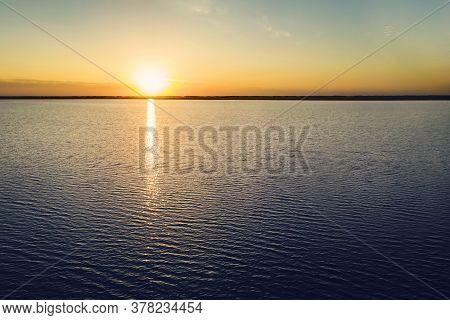 Sunset At Coast Of The Sea. Yellow Sun Sets Behind The Lake. Beautiful Sunset On The Lake. Beautiful