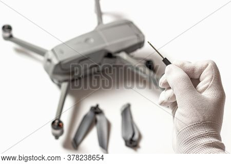 Quadrocopter And Hand In White Glove With A Screwdriver, Drone Repair Concept.