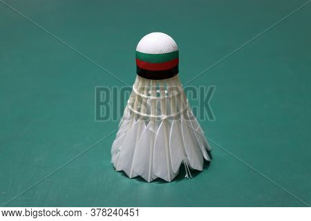 Used Shuttlecock And On Head Painted With Bulgaria Flag Put Vertical On Green Floor Of Badminton Cou