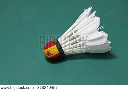 Used Shuttlecock And On Head Painted With Spain Flag Put Horizontal On Green Floor Of Badminton Cour
