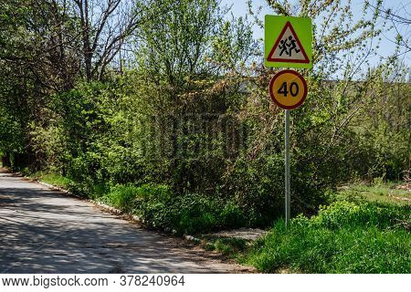 Two Road Signs On One Pillar Caution Children Sign And Speed Limit Sign 40. Signs On The Background