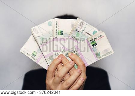 A Lot Of Money In The Hand Of A Young Businessman On A Blue Background. A Stack Of Banknotes Of Russ
