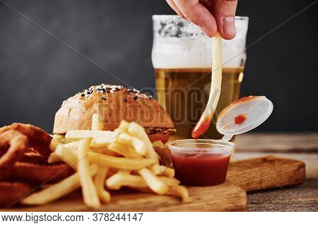 Different Types Of Fastfood And Snacks And Glass Of Beer On Table. Unhealthy And Junk Food.