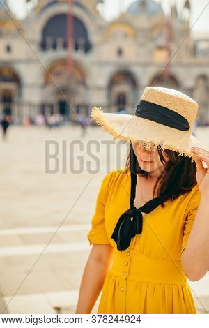 Woman In Yellow Sundress Outdoors Hiding Eyes Behind Big Straw Hat