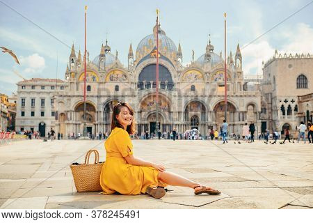 Woman In Yellow Sundress Sitting On The Ground Enjoying The View Of Saint Marco Basilica