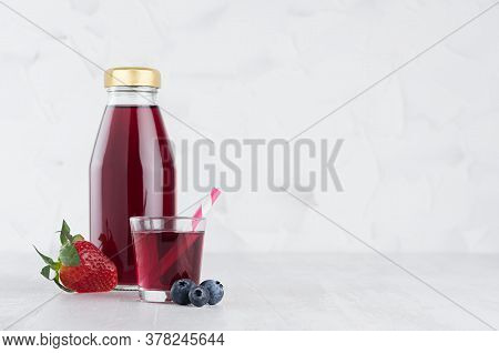 Fresh Purple Berries Juice In Glass Bottle Mock Up With Blueberry, Strawberry, Glass, Straw In Soft