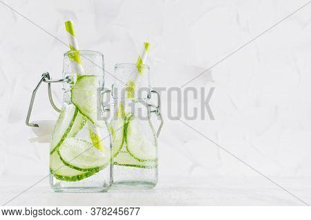 Fresh Summer Cocktails With Green Cucumber, Soda, Straw In Yoke Bottles On Elegant Soft Light White