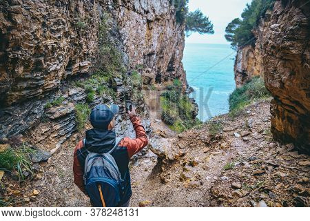 Man With Backpack At Footpath Canyon Leading To Sea Beach Taking Picture On The Phone