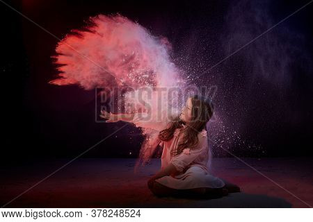 Small Girl In White Dress In Dark Studo During Photoshoot With Flour. Young Model Posing With White