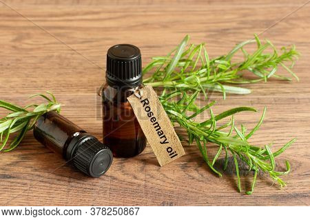 Bottle Of Rosemary Essential Oil And Fresh Rosemary Branch On Wooden Background.