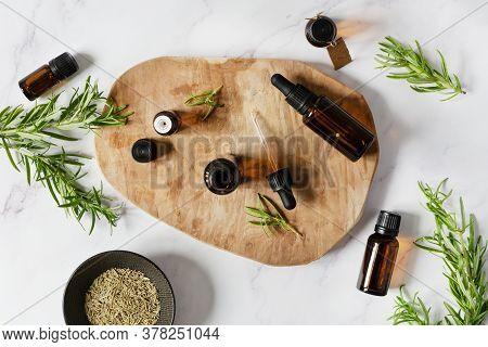 Rosemary Essential Oil And Fresh Rosemary Branch On White Marble Background.