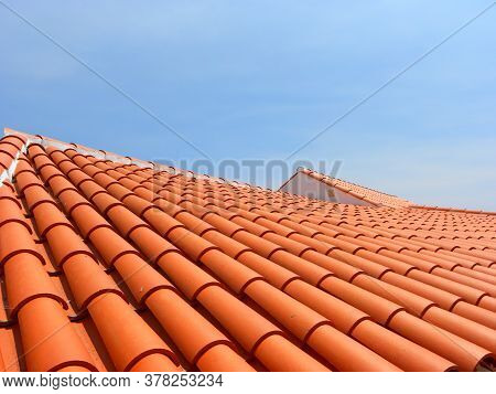 Red Tile Roof Under Blue Sky. The Photo Is Divided In Half. One Part Is A Roof Made Of Clay Tiles An