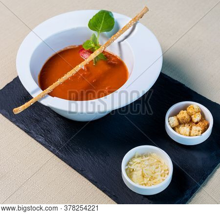Tomato Red Soup With Bread Crumbs On The Black Plate