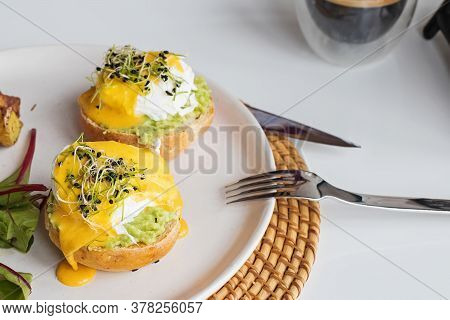 Poached Eggs Over The Bread Bun With Mashed Avocado.