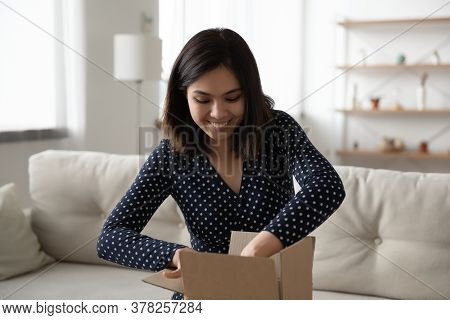 Excited Asian Woman Unpack Postal Package At Home