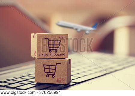 Cardboard Box On Notebook Keyboard. Online Shopping, E-commerce And Delivery Service Concept. Produc