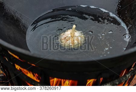 Cooking Rice Pilaf In A Large Cast Iron Pot Over A Fire. Garlic Bulb In Boiling Oil