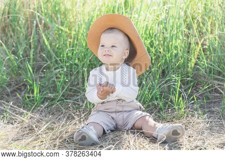 Beautiful Blond Baby In A Hat And Suit With Suspenders Sits In The Dry Grass