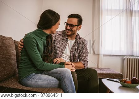Happy Couple Is Relaxing And Talking At Home.