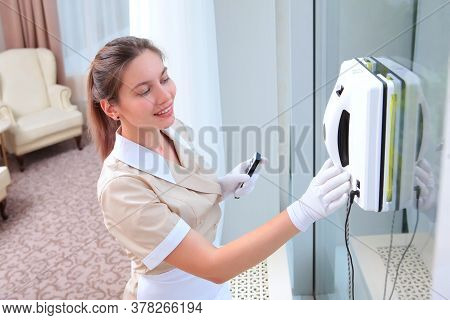 Robot For Washing Windows. Cleaning Of Hotel Rooms. The Maid Begins To Wash The Windows. Copy Of The