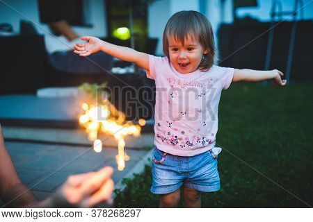 Child Seeing Sparkler Fireworks First Time Outside. Happy And Excited 2 Years Old.