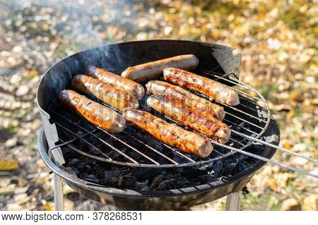 Bbq Sausages Are Cooked On The Grill In The Meadow In The Park On A Sunny Autumn Day. Delicious Juic