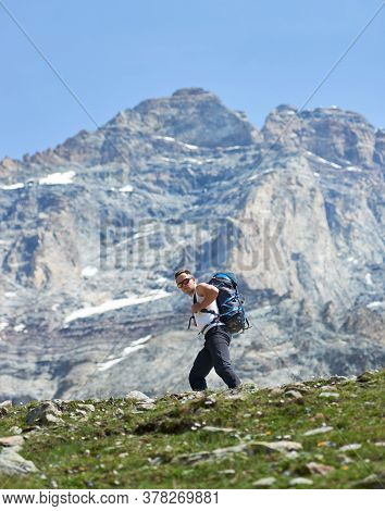 Male Mountaineer In Sunglasses Hiking Alone In Mountainous Region. Hiker With Backpack Walking Along
