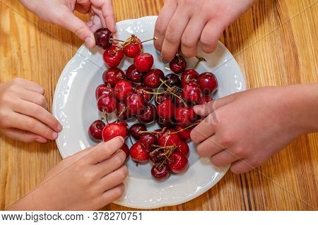 Many Children Hands Grab Sweet Cherries From A Plate On A Wooden Table