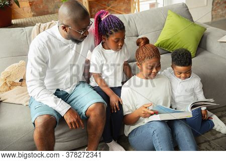 Books Reading. Young And Cheerful African Family During Quarantine, Insulation Spending Time Togethe