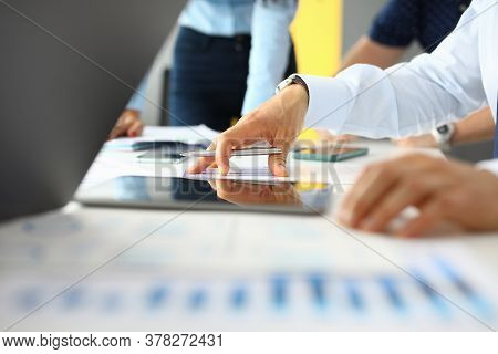 Workplace In Business Office On Table Are Tablet Documents Co-workers Hold Pens In Their Hands. Busi