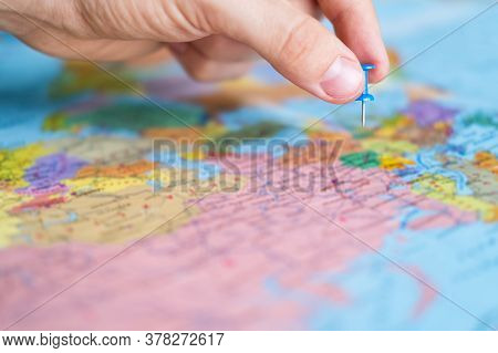 Man Pins A New Destination On A World Map, For His Next Trip. Travel Destination, Pin On The Map. Ve
