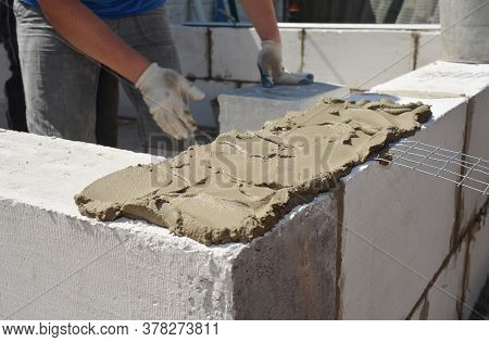 A Building Contractor Is Applying A Generous Amount Of Mortar With A Spade Mortar To Bricklaying A W