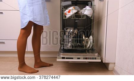 Woman Loading Dishes In The Dishwasher, High Angle View Of Dishes In The Dishwasher In The Kitchen