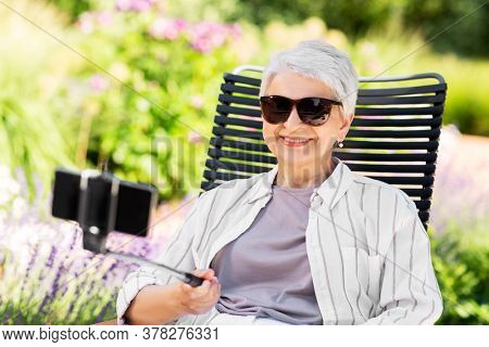 technology, old age and people concept - happy smiling senior woman with smartphone on selfie stick taking picture at summer garden