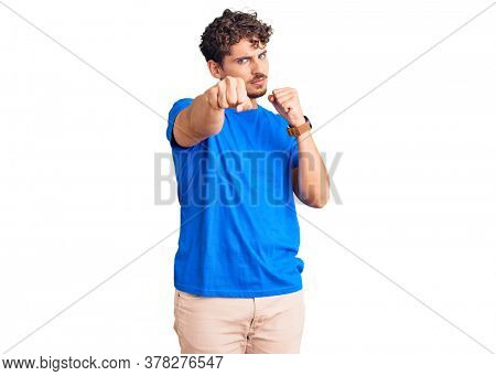 Young handsome man with curly hair wearing casual clothes punching fist to fight, aggressive and angry attack, threat and violence
