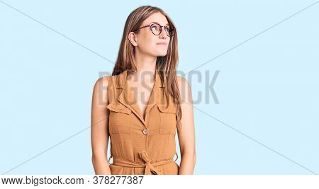 Young beautiful blonde woman wearing casual clothes and glasses smiling looking to the side and staring away thinking.