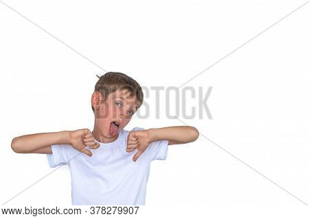 Portrait Of An Unhappy, Unhappy Boy Stuck Out His Tongue Making Thumbs Down Hand Gesture, Isolated W