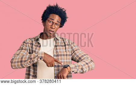 Handsome african american man with afro hair wearing casual clothes and glasses in hurry pointing to watch time, impatience, upset and angry for deadline delay