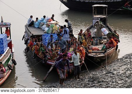 SUNDARBANS, INDIA - FEBRUARY 26, 2020: Wooden boat crosses the Ganges River in Sundarbans, West Bengal, India