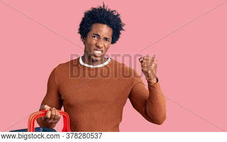 Handsome african american man with afro hair holding supermarket shopping basket annoyed and frustrated shouting with anger, yelling crazy with anger and hand raised