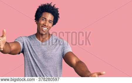 Handsome african american man with afro hair wearing casual clothes looking at the camera smiling with open arms for hug. cheerful expression embracing happiness.