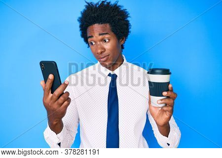 Handsome african american man with afro hair using smartphone and drinking a cup of coffee smiling looking to the side and staring away thinking.