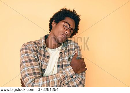 Handsome african american man with afro hair wearing casual clothes and glasses hugging oneself happy and positive, smiling confident. self love and self care