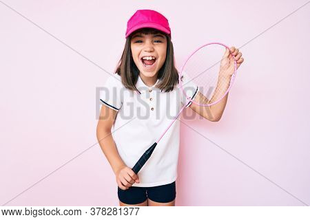 Young little girl with bang holding badminton racket smiling and laughing hard out loud because funny crazy joke.