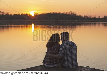 Young Couple In Love Camping On Lake Docks, Hugging, Kissing And Enjoying Beautiful Sunset Over The