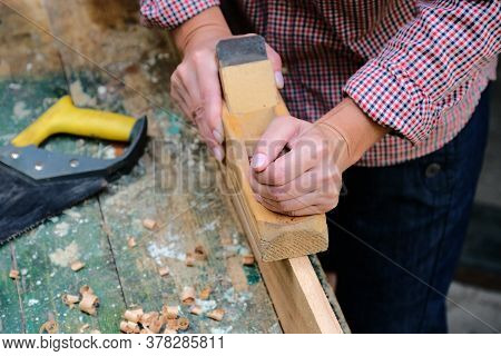 Female Carpenter Works With Wood Planer In Workshop. Top View Workbench In Carpenter's Shop.