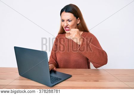 Young brunette woman working using computer laptop annoyed and frustrated shouting with anger, yelling crazy with anger and hand raised